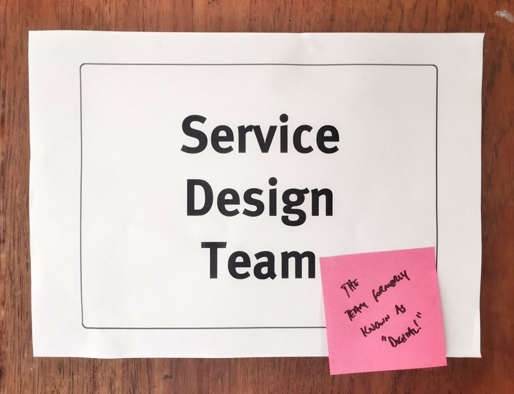 a sign saying 'service design team' with a stickly note on it saying 'the team formerly known as 'digital''