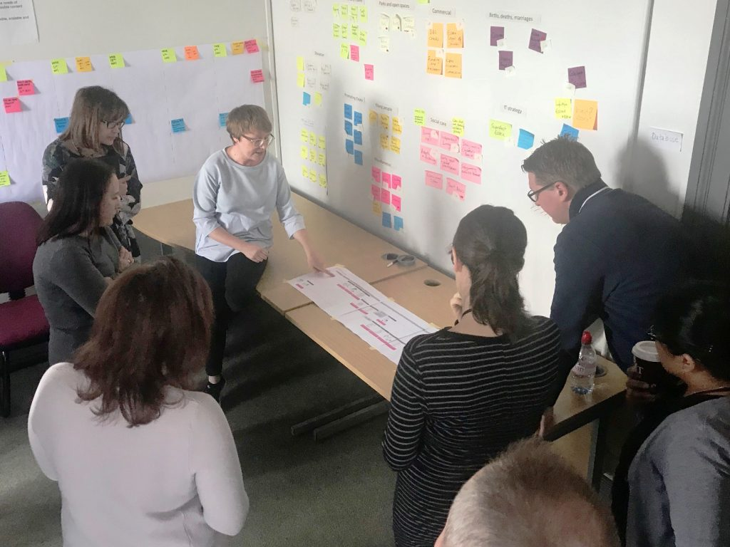 a mixed group of people standing around a desk and learning about the customer journey