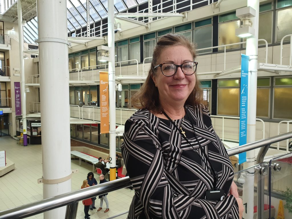 Caroline, content designer standing on the bridge with County Hall atrium in the background